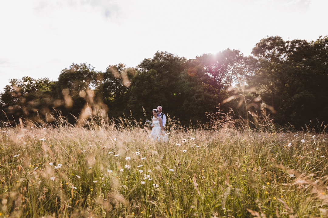 bride-and-groom-in-widlflower-meadow-jen-and-mat's-festival-wedding-at-Scraptoft farm